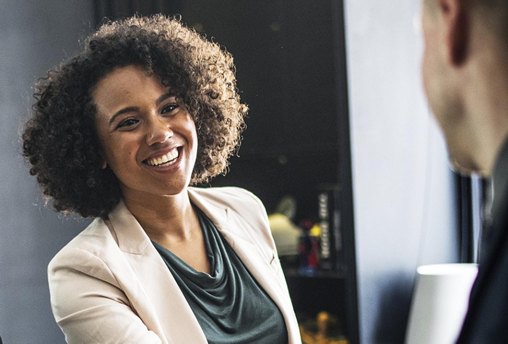 基本のビジネス英語「自己紹介」について解説する記事中のイメージ画像です。笑顔で談笑する女性の姿が写っています。