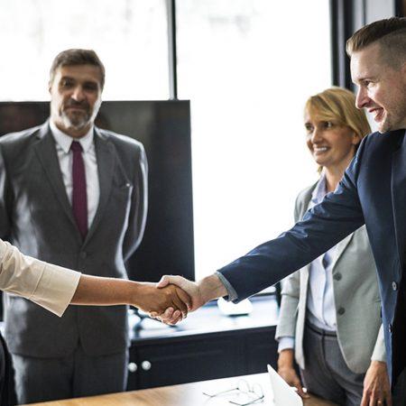 基本のビジネス英語「挨拶」について解説する記事中のイメージ画像です。数人のビジネスパーソンが輪になって立っており、手前の2人が笑顔で握手しています。