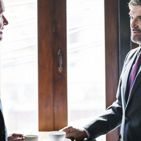 海外でのビジネス交渉のコツについて解説する記事中のイメージ画像です。ティーテーブルを挟んで話し合う2人の男性の姿が写っています。背景は大きな窓でカフェ店内のようです。