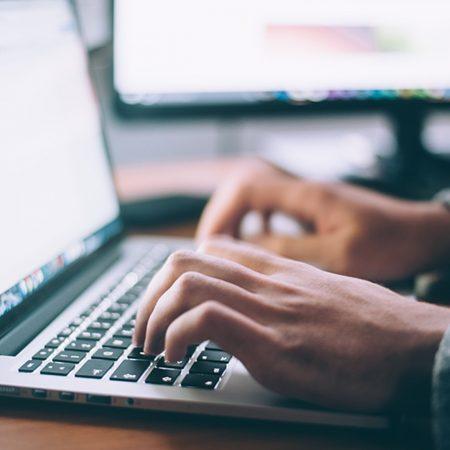 初心者でも始められる輸入ビジネスについて解説した記事中のイメージ画像です。キーを叩いてノートパソコンになにやら打ち込む人物の手のアップ画像です。