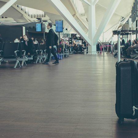 海外出張時などで持っていくスーツケースのサイズの選び方について解説した記事中のイメージ画像です。空港ロビーに置かれたスーツケースを写しています。