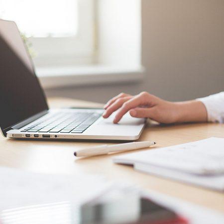 輸入ビジネスの魅力と始め方について解説した記事中のイメージ画像です。ノートPCを片手で軽く扱う女性の姿が写っています。