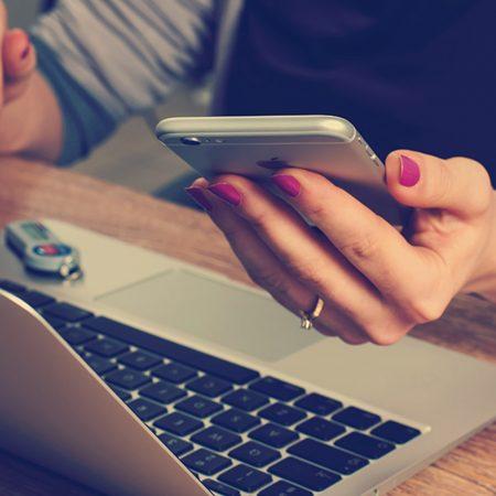 輸入ビジネスを副業として収入源を増やす、その方法について書かれた記事中のイメージ画像です。ノートパソコンを開いた女性がスマホの画面に目を奪われています。