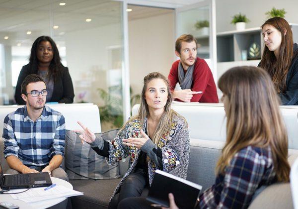 海外におけるビジネス交渉をスムーズに進めるためのコツについて解説した記事中のイメージ画像です。数名の男女が会議室に集まり何やらディスカッションしています。