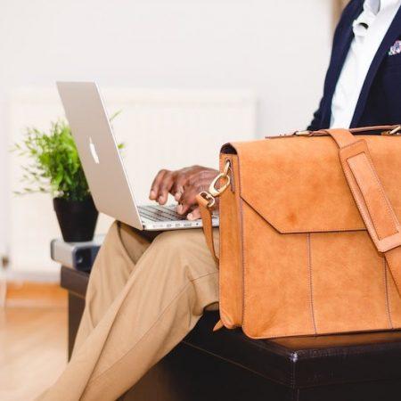 海外出張の服装について説明した記事内のイメージ画像です。空港ロビーの椅子に腰掛けた人物がカバンを脇に置きノートPCを開いて膝に置いています。