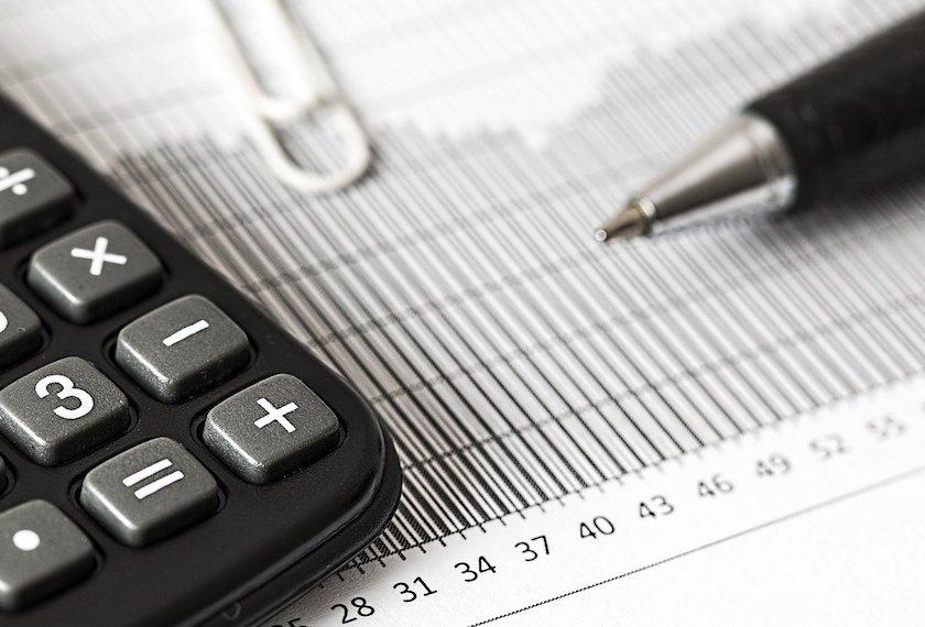 個人の輸入ビジネスにかかる関税のルールと手続きを知るための記事中のイメージ画像です。ボールペンと電卓、グラフの書かれた用紙が置かれています。