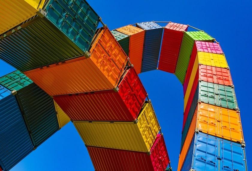 関税について説明する記事中のイメージ画像です。鮮やかな青空を背景にいろとりどりのコンテナが複雑な曲線を描きます。