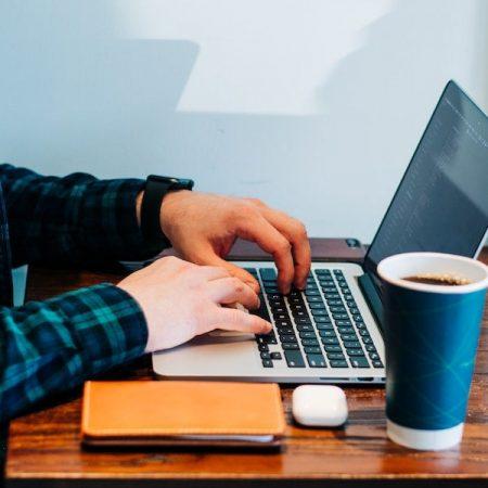 英語のビジネスメール、結びの書き方についての記事中のイメージ画像です。卓上で人物がノートパソコンを操っています。