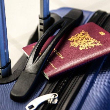 海外出張の必需品について書かれた記事中のイメージ画像です。スーツケースの上に赤いパスポートが置かれています。